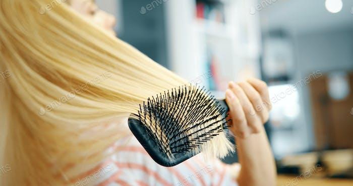 Привлекательная улыбающаяся женщина чистить ее волосы