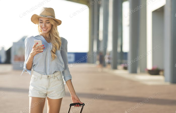 Female tourist walking with baggage at airport terminal