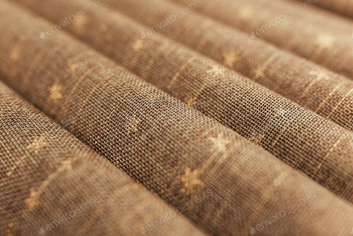 Folds of brown textile tablecloth. Blurred background