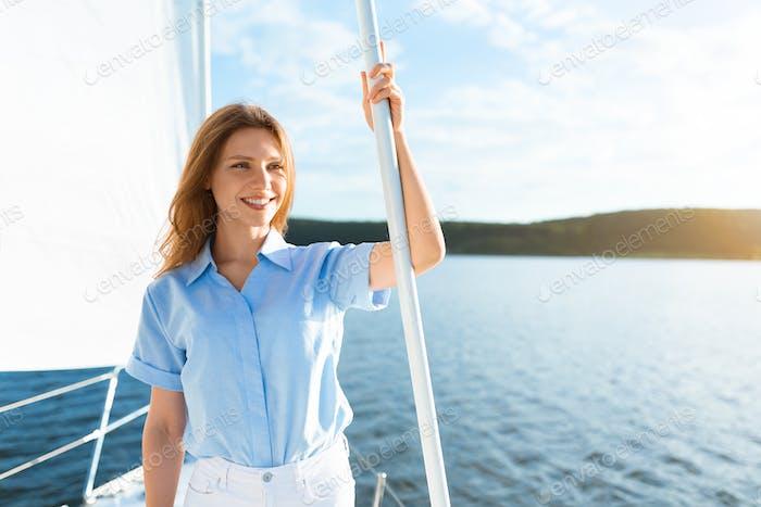 Lady Sailing On Sailboat Standing On Deck Enjoying Yacht Ride