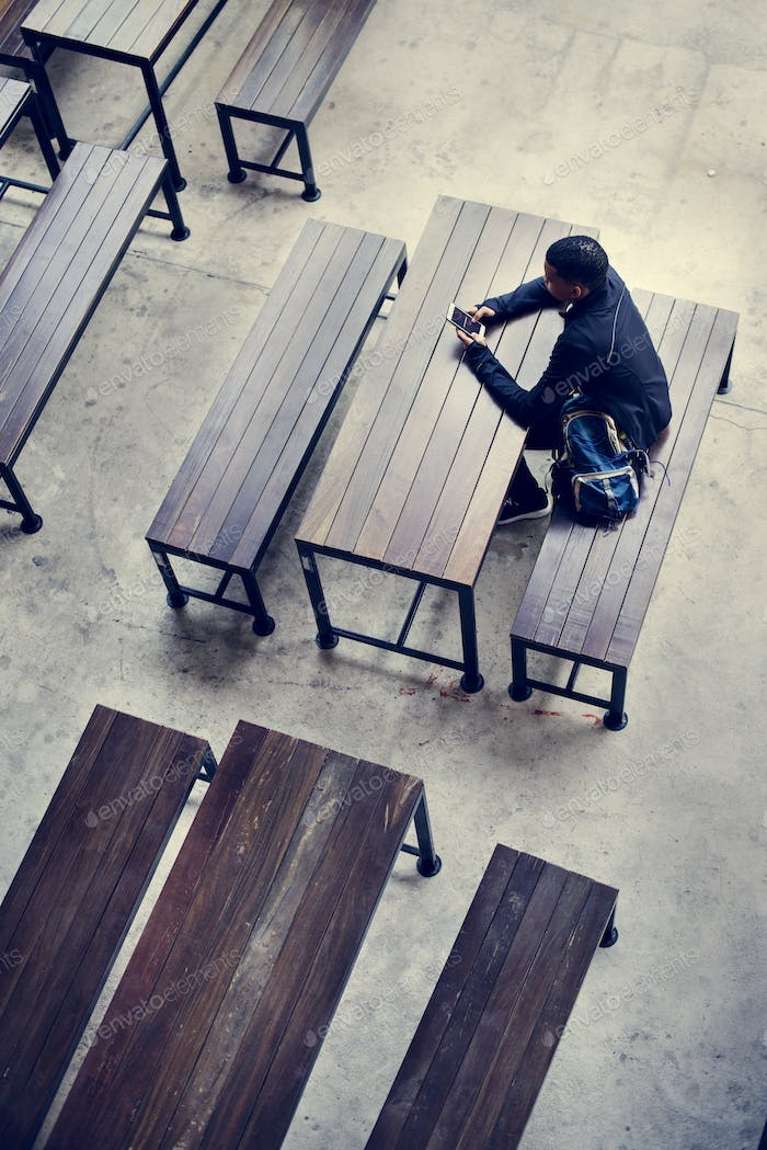 Teenage boy sitting alone in an empty canteen