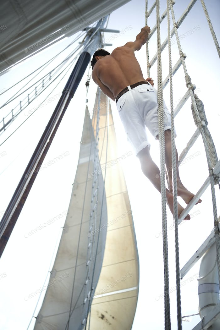 A man in white shorts with bare chest climbing up the rigging of a sailing boat.