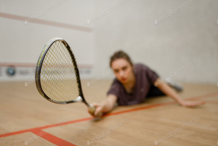 Female player with squash racket lies on the floor