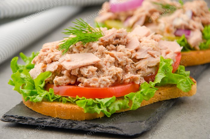 Tuna sandwiches with lettuce tomatoes pickles and onions on slate tray