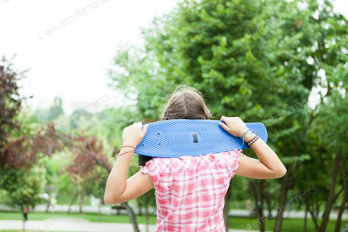 Happy girl holds a blue skateboard on her shoulders in the park