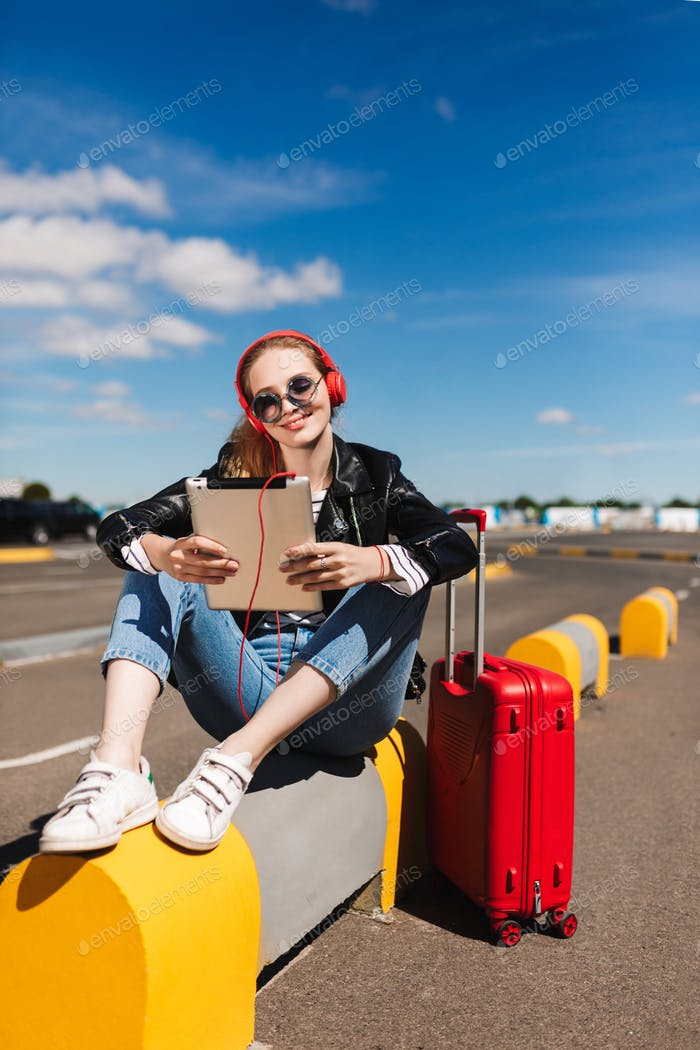 Smiling girl in sunglasses and headphones happily listening musi