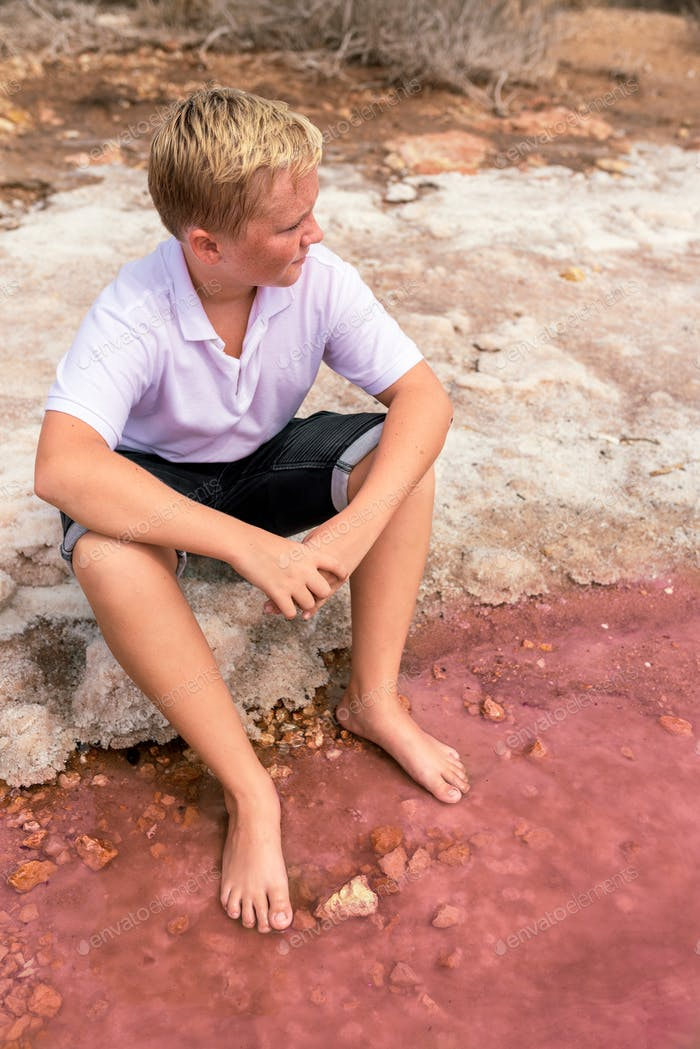 cute teenager blonde boy wearing summer clothes sitting on shore of an amazing pink lake