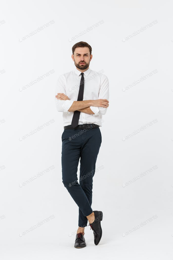 Portrait of a confident young businessman with hands in pockets on white background