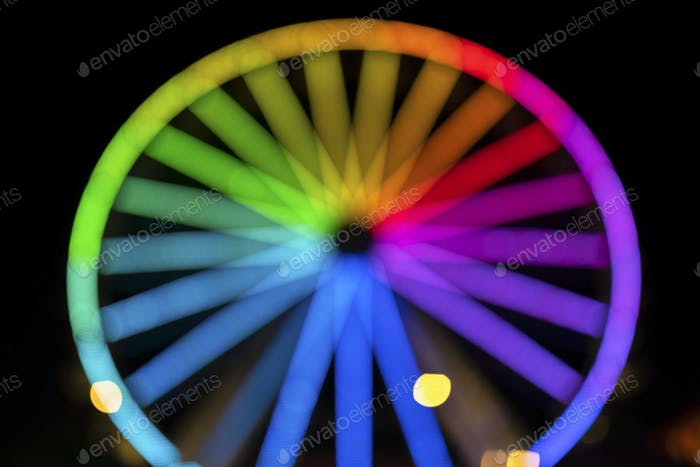 Blurry colorful neon Ferris wheel in a carnival at night