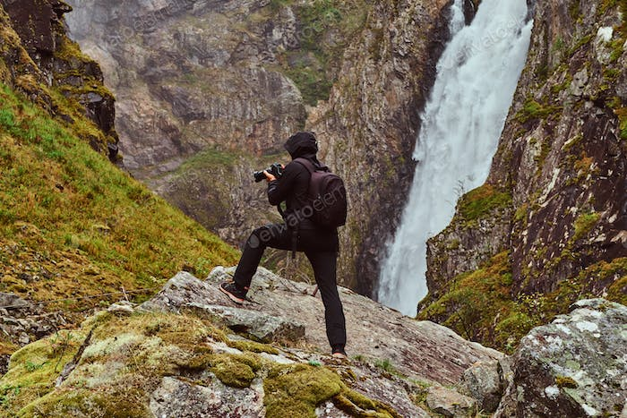 Nature photographer tourist with camera shoots while standing on the mountain against a waterfall