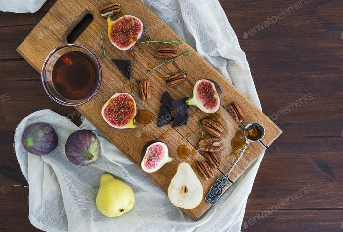Fresh figs, pears and pekan nuts with honey on a wooden board