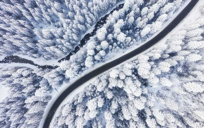 Road and winter forest from air. Winter aerial landscape. View from drone