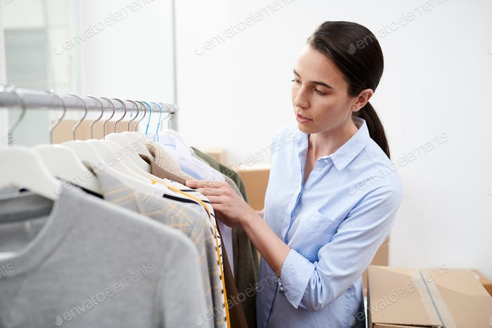 Young designer of clothes looking through new collection of casualwear in studio