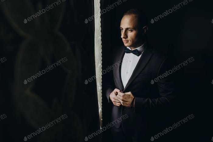 Stylish groom portrait at the window while getting ready in the morning