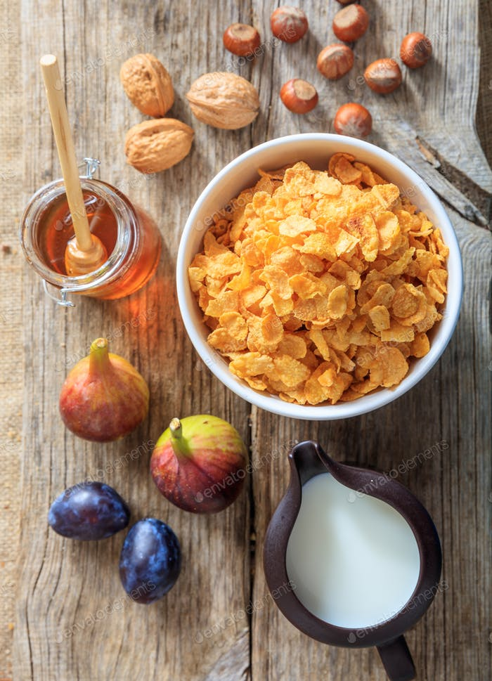 Breakfast concept. Bowl with corn flakes, fruits and nuts on wooden background.