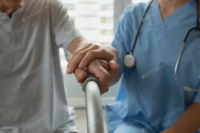 Mid section of Caucasian female doctor consoling active senior man at home