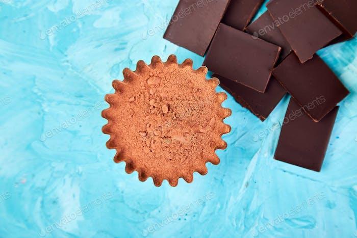 Kakaobohnen Hintergrund auf blauem Tisch. Zartbitterschokolade Stücke