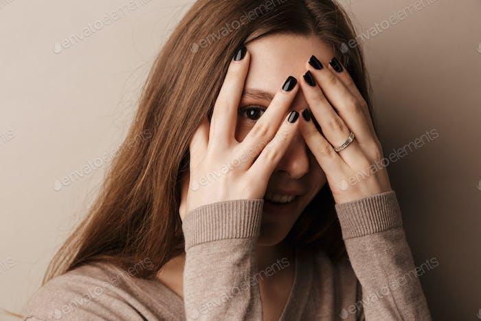 Foto de joven mujer feliz sonriendo y cubriendo sus ojos