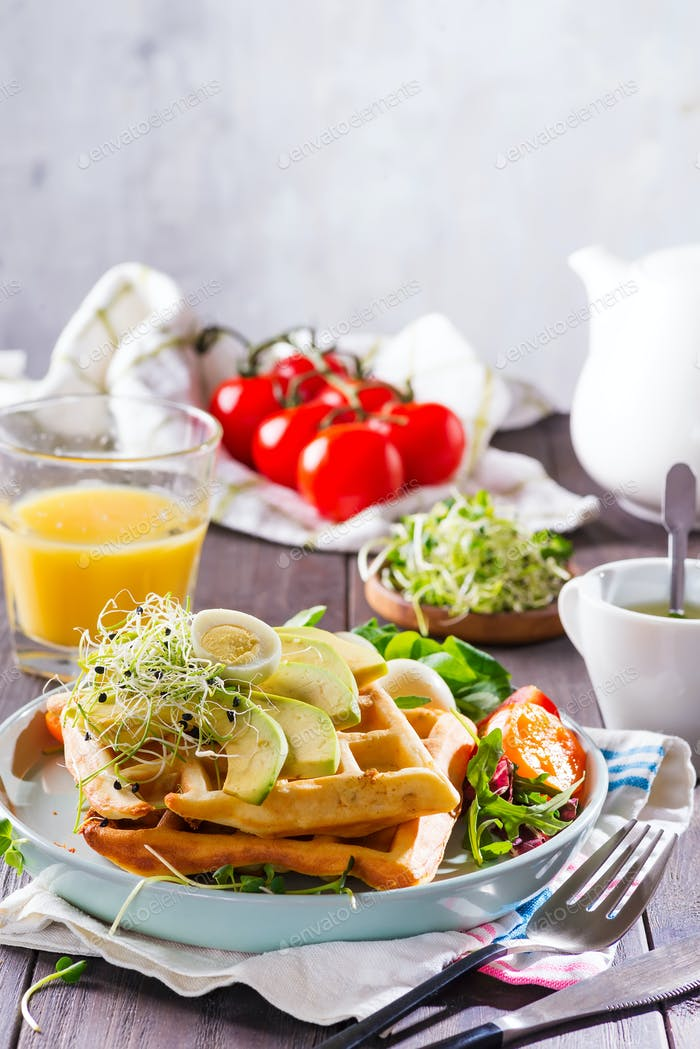 Breakfast time. Waffle with salad, egg, juice and avocados for breakfast