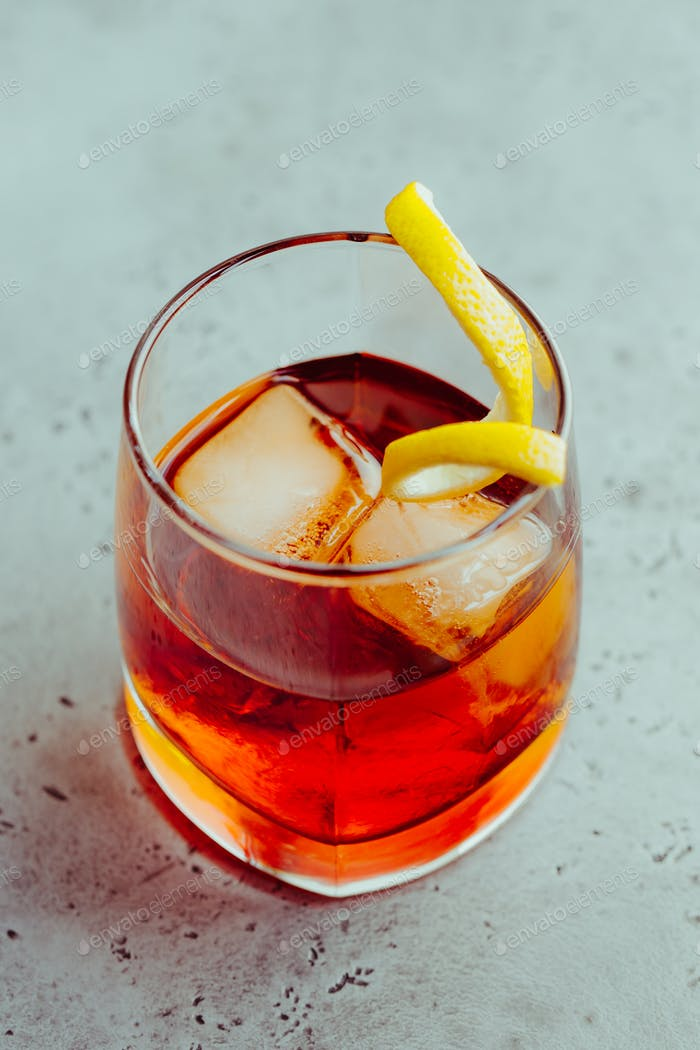 Cocktail with bitter and rye whiskey served lemon twist.