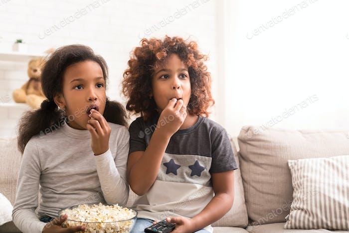Interessierte Mädchen beobachten Entdeckung Film und Essen Popcorn