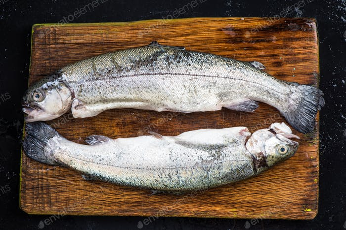 Raw trout fresh fish on wooden board,top view