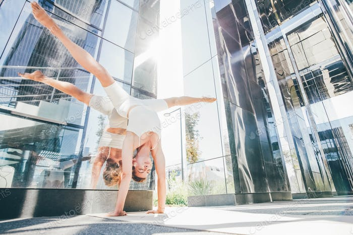 Woman practicing yoga outdoors in city against urban cityscape.