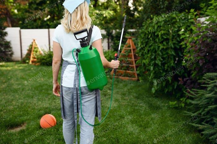 Woman in apron watering flowers in the garden