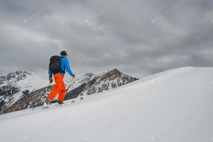 Man with ski mountaineering climb towards the summit