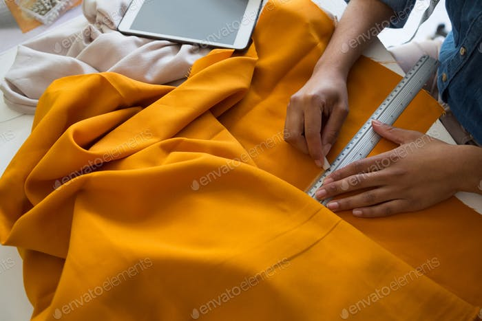 Mid section of female fashion designer marking on fabric
