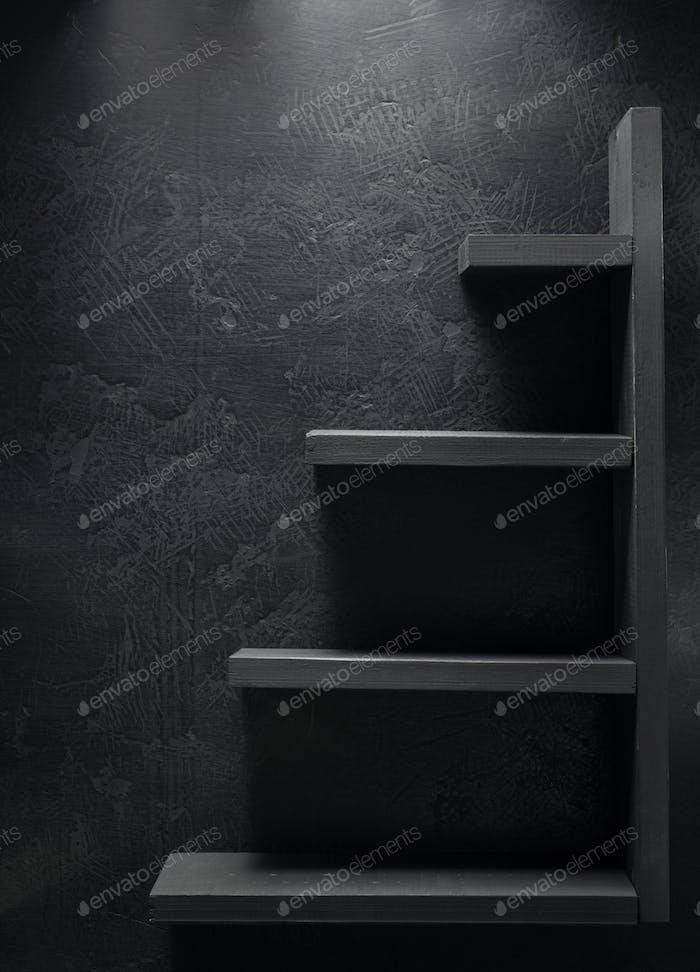 wooden shelf at black wall