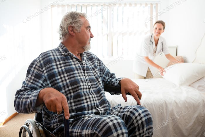 Thumbnail for Senior man looking at doctor adjusting bed while sitting on wheelchair