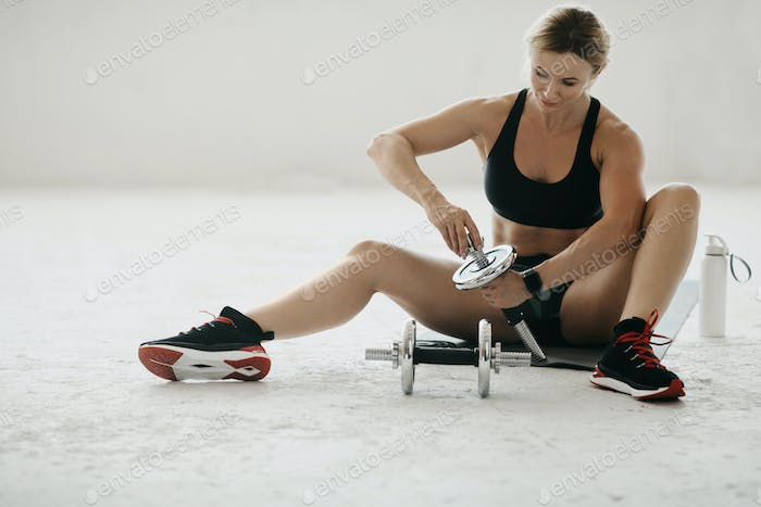 Middle age woman in sportswear puts disks on dumbbells sits on mat on floor