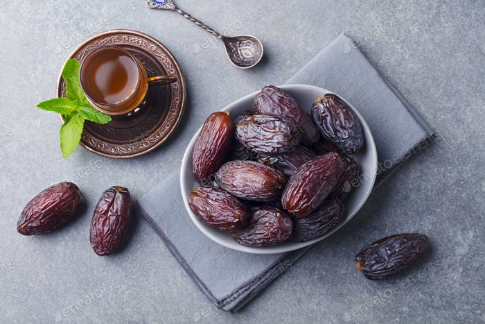 Fresh Medjool Dates in Bowl with Tea. Ramadan Kareem. Grey Stone Background. Top View.