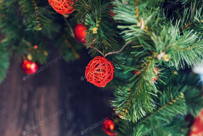 Closeup of red baubles hanging from a decorated Christmas tree.