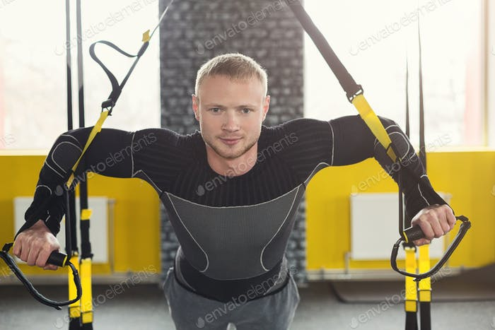 Man performing TRX suspension training in gym