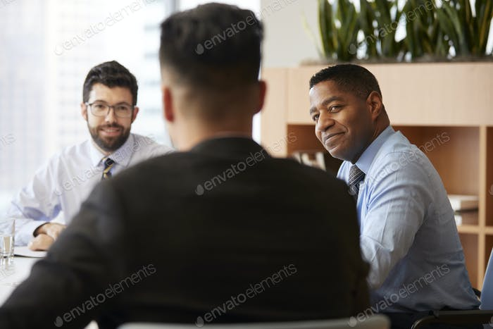 Three Businessmen Sitting Around Table Meeting In Modern Open Plan Office