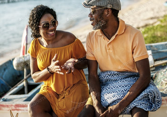 Black couple taling cheerful at the beach together