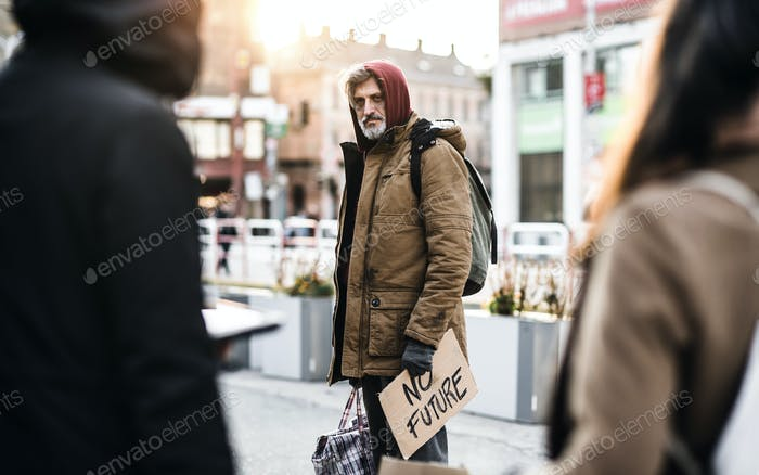 Homeless beggar man walking outdoors in city, holding bag and cardboard sign.