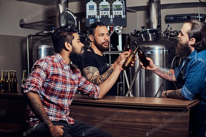 Three bearded interracial friends drink craft beer in a brewery.