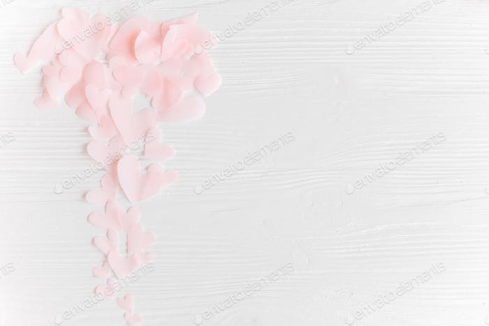 Cute pink pastel hearts on white wooden background with space for text