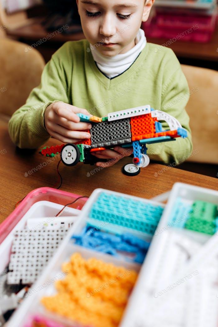 Fokussierte Junge in grünen Pullover gekleidet sitzt am Tisch in der Robotikschule und macht einen Roboter aus
