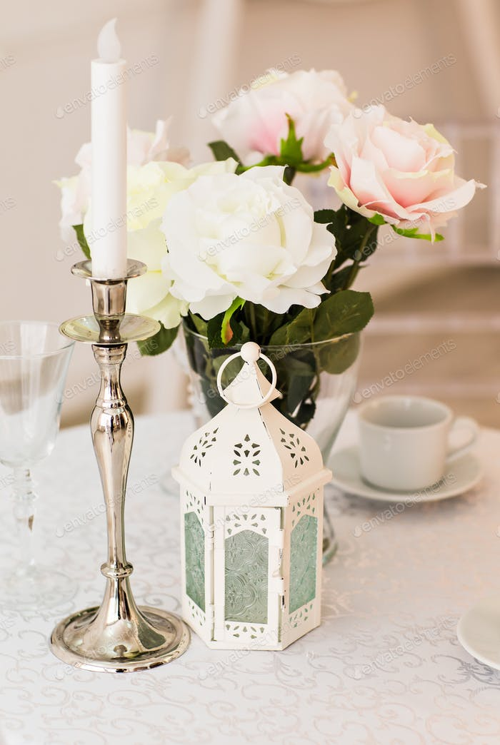 Vintage interior with candle lanterns  flowers and a cup