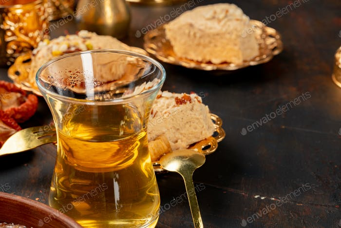 Glass cup of tes and turkish desserts on table