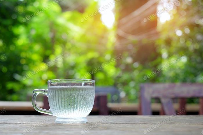 Glaswasser auf Holztisch mit grünen verschwommenen Hintergrund.