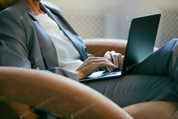 Businesswoman Using Laptop in Lounge Chair