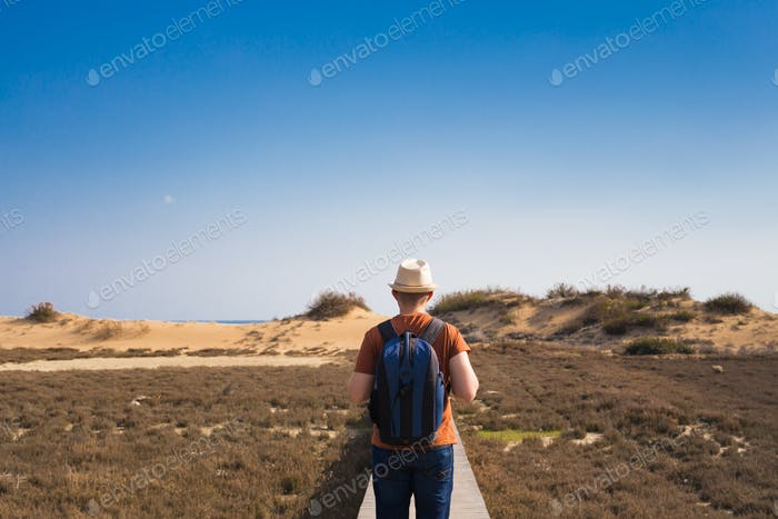 Outdoors lifestyle image of travelling man back view. Tourism concept.