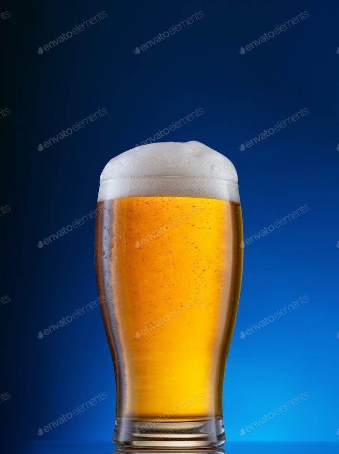 Verre à la bière légère sur fond bleu