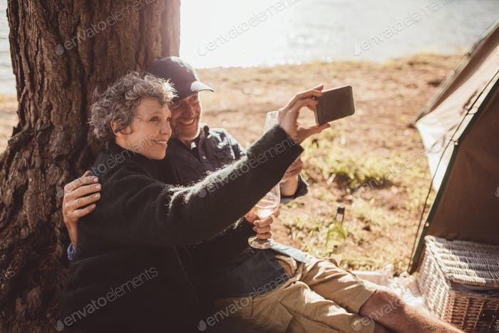 Mature couple camping near a lake taking selfie