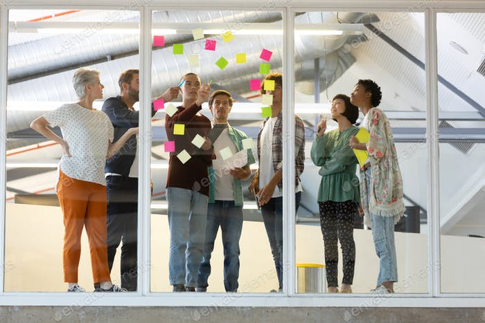 Front view of diverse business people discussing over sticky notes in the modern office